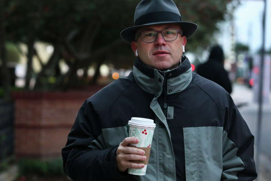 Simon Trubek walks back to his home with his morning coffee from Starbucks in the high-30s weather on Tuesday, Nov. 13, 2018, in Houston.