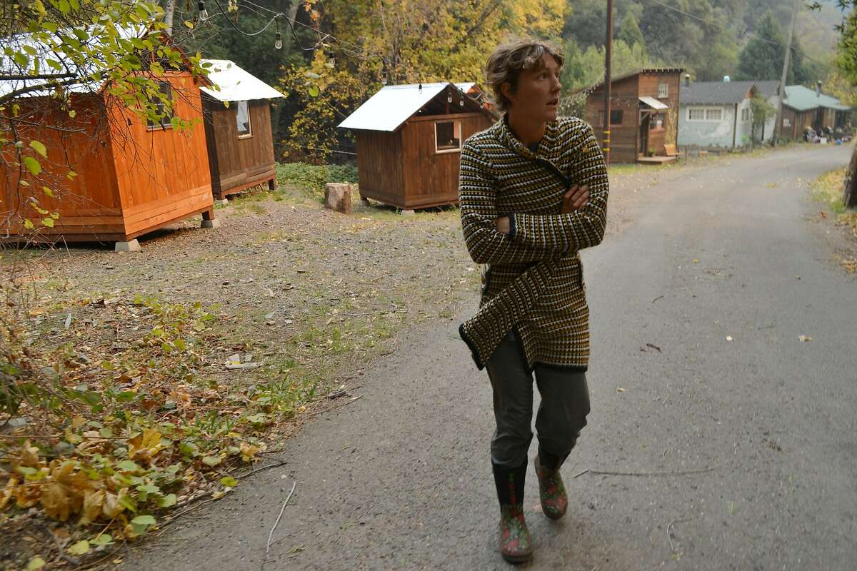 Betsy Ann Cowley walks through Pulga, Calif., during an interview Monday, Nov. 12, 2018, near where investigators were trying to determine the cause of the deadly fire that destroyed the town of Paradise. A day before a deadly blaze destroyed a California town, the giant utility Pacific Gas & Electric Co. got in touch with Cowley, saying they needed access to her property because their power lines were causing sparks. (AP Photo/Peter Banda)