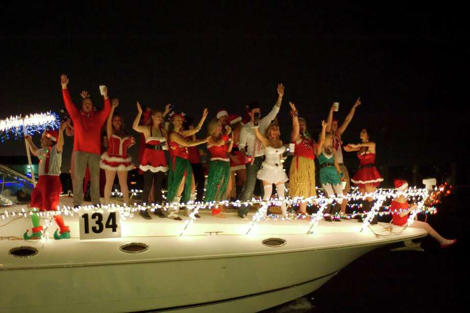 Costumed dancers line the deck of a decorated boat during the League City Annual Boat Lane Parade. Photo: Kirk Sides, MBR / Associated Press / The Courier