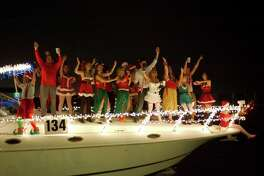 Costumed dancers line the deck of a decorated boat during the League City Annual Boat Lane Parade.