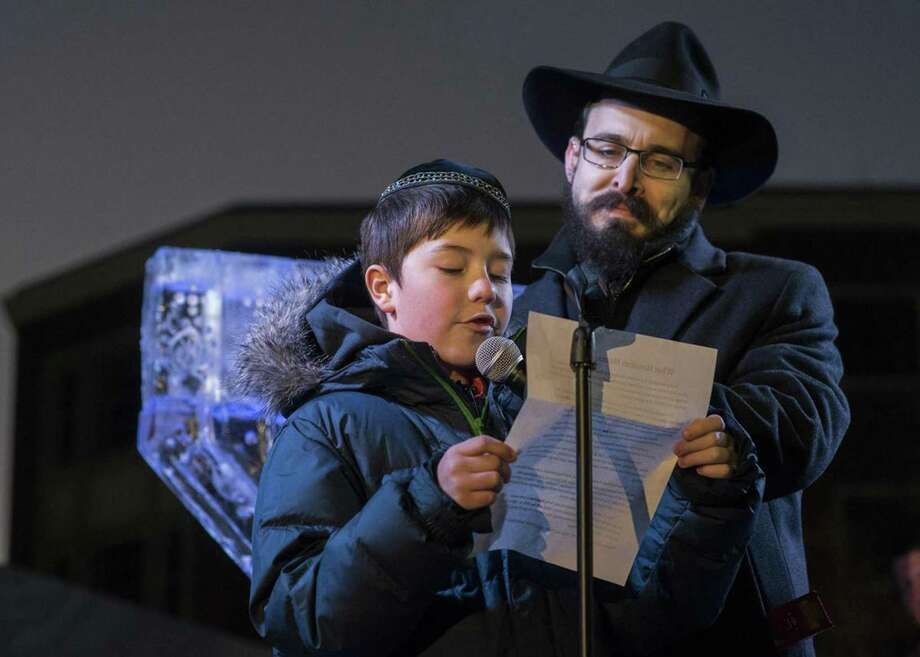 Prior essay winner Mark Kirzon reads his essay to the crowd, while Rabbi Shaya Gopin looks on. Photo: Chabad Of Greater Hartford /Contributed