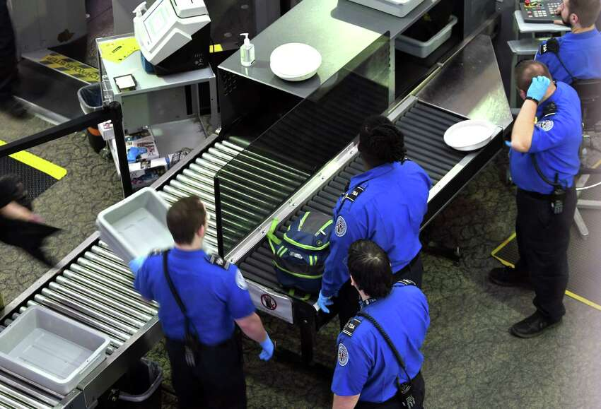 TSA agents inspect carry-on luggage at Albany International Airport on Tuesday, Nov. 13, 2018, in Colonie, N.Y. (Will Waldron/Times Union)