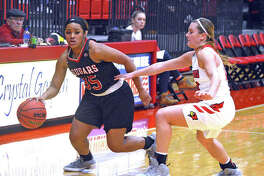 SIUE freshman Mikala Hall, left, dribbles past an Illinois State defender during Sunday's season opener at Vadalabene Center.