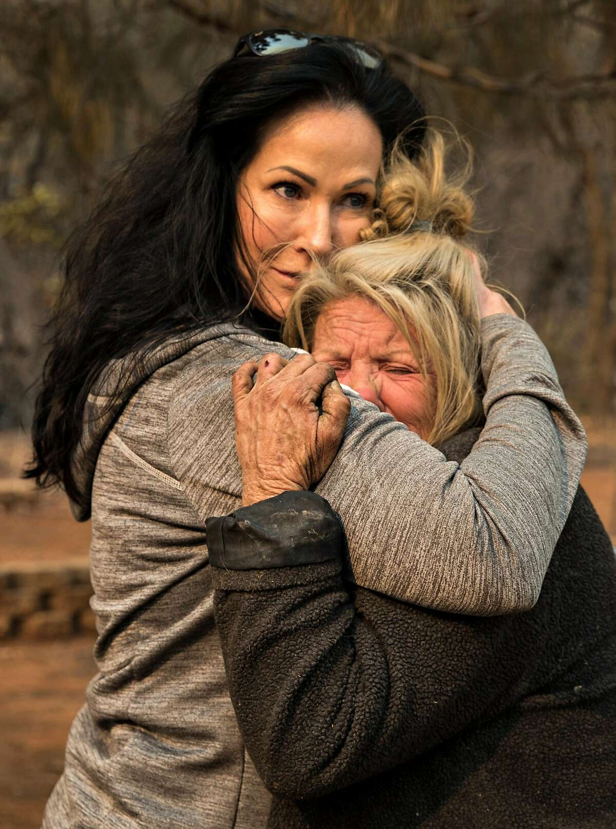 Animal volunteer evacuator Tamara Houston, left, comforts Cathy Fallon outside Fallon's home Sunday, Nov. 11, 2018. Fallon survived the Camp Fire while bunkering down in her home on Edgewood Lane after the Camp Fire ripped through the town of Paradise, Calif.