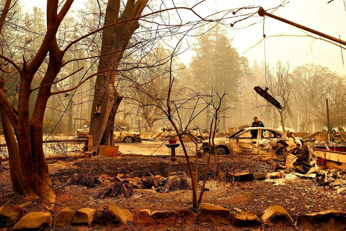 Alameda County Sheriff's Dept. Sgt. Howard Baron looks in a burned vehicle while searching for fire victims in the Rocky Lane Mobile Home Park in aftermath of Camp Fire in Paradise, Calif. on Monday, November 12, 2018.