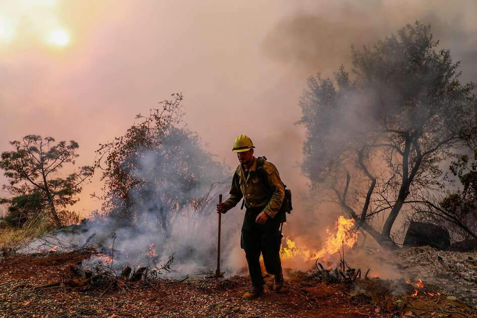 Hotshot firefighter works to stave off the Camp Fire as it burns off of Pentz Road in Paradise, California, on Thursday, Nov. 8, 2018.