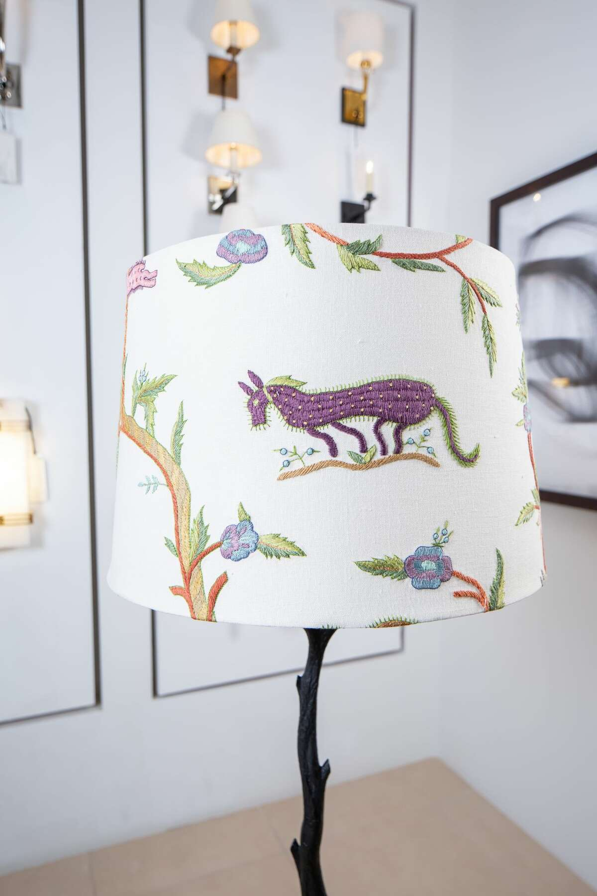 The lampshade has soft natural colors and shows tree branches, flowers and horses.