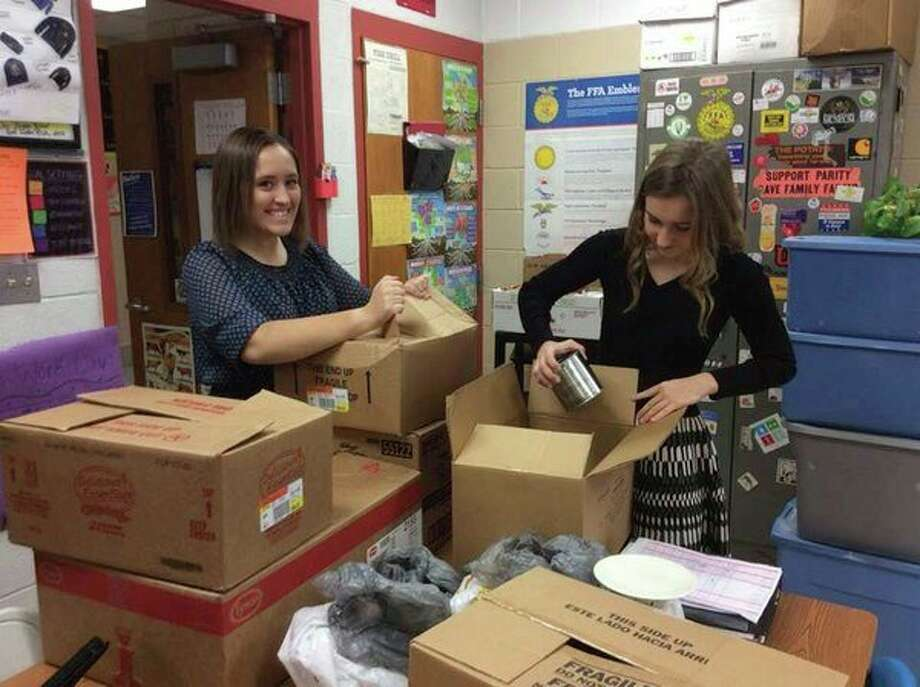 Kylie Ogryski, left, and Cheyenne Porzondek are pictured packing up food to take to the Parish Center. Harvest for America is a great way to give to families in need in your community. Ubly FFA collects nonperishable food items and money from September to February. $1 equals three pounds of food. They will be raffling off a Carhart coat in TSC now through Feb. 23, 2019. They also do a competition within the school classes through Nov. 23. (Submitted Photo)