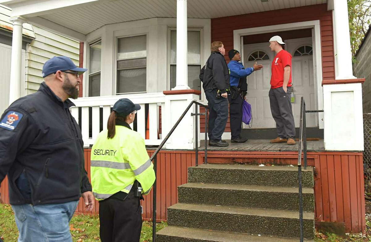 Members of New York State Office of Fire Prevention and Control, state and local fire departments and Albany police talk to a resident of an apartment during a fire prevention outreach program near Saint Rose Safety & Security Headquarters on Tuesday, Nov. 13, 2018 in Albany, N.Y. The fire prevention and safety measures were made so residents can take in the wake of the recent fires, including the Pine Hills fire on Quail Street in late September. (Lori Van Buren/Times Union)
