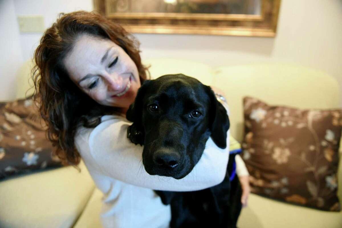 Laura Assaf holds Jenny, a service dog puppy she is raising for Canine Companions for Independence on Monday, Oct. 29, 2018, in Rotterdam N.Y. CCI provides assistance dogs free of charge to adults, children and veterans with disabilities. (Will Waldron/Times Union)