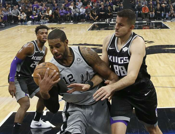 San Antonio Spurs forward LaMarcus Aldridge, center, grabs a rebound against Sacramento Kings forward Nemanja Bjelica, right, as Kings guard Buddy Hield, left, looks on during the second half of an NBA basketball game, Monday, Nov. 12, 2018, in Sacramento, Calif. The Kings won 104-99. (AP Photo/Rich Pedroncelli)