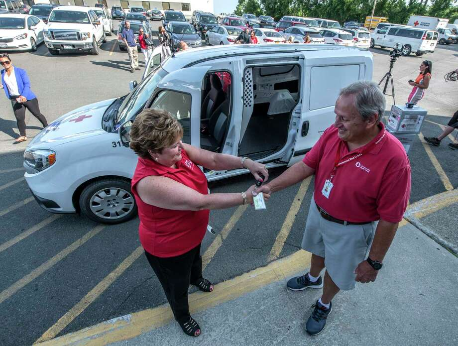 The American Red Cross added a new blood transport vehicle to its fleet based locally thanks to a donation from CAP COM Federal Credit Union Friday July 13, 2018 in Albany, N.Y.  Paula Stopera, president and CEO, CAP COM FCU, left makes a ceremonial presentation of the key to the new vehicle to Red Cross volunteer Ed Breen.   (Skip Dickstein/Times Union) Photo: SKIP DICKSTEIN / 20044318A