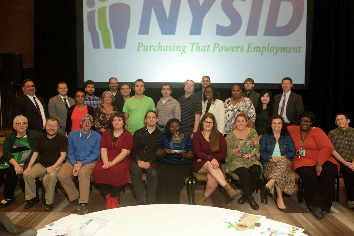 EBizDocs President Howard Gross, standing far left, accepts the Corporate Partner of the Year award from New York State Industries for the Disabled Inc. last month along with many of his employees, including Tobi Bickweat, human resources manager and productivity coordinator, seated far left. (Submitted photo)