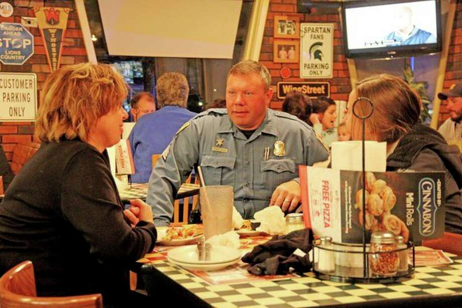 Bad Axe Sergeant Mike Anderson talks with customers between waiting tables during 'Tips Night' at the Bad Axe Pizza Hut. The event raised $1,444 for the Shop with a Hero program, which allows students from under privileged families in Huron County an opportunity to shop for Christmas presents for family members. (Mike Gallagher/Huron Daily Tribune)