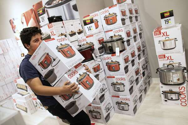 FILE- In this Nov. 23, 2017, file photo Joaquin Haces Garcia caries crockpots through JC Penney shortly after their 2 p.m. opening on Thanksgiving Day in Corpus Christi, Texas. A solid 70 percent of Americans plan to shop on Black Friday this year, according to a recent NerdWallet study conducted by The Harris Poll. (Courtney Sacco/Corpus Christi Caller-Times via AP, File)