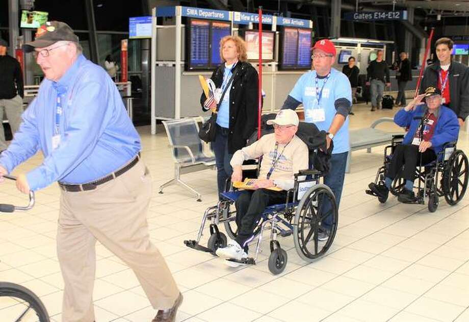 Bob White, of Edwardsville, a veteran of both World War II and the Korean War, center, is escorted by his son, David White, through Lambert International Airport on Saturday after taking part in a Greater St. Louis Honor Flight to Washington, D.C. Photo: For The Telegraph