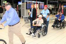 Bob White, of Edwardsville, a veteran of both World War II and the Korean War, center, is escorted by his son, David White, through Lambert International Airport on Saturday after taking part in a Greater St. Louis Honor Flight to Washington, D.C.