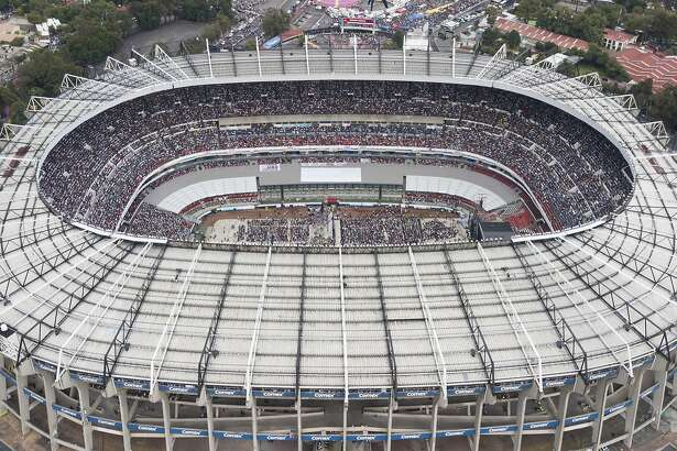 FILE - In this June 27, 2018, file photo, supporters of presidential candidate Andres Manuel Lopez Obrador, of the MORENA party, fill Azteca stadium as they wait for him to arrive for his closing campaign rally in Mexico City. The abused hybrid grass of the Azteca Stadium is generating concerns for its poor condition a week before it hosts an NFL regular-season game between the Los Angeles Rams and the Kansas City Chiefs. Last May, stadium authorities changed the surface from natural to hybrid. But the intense activity in the last few months has prevented the grass from reaching an optimum state. (AP Photo/Christian Palma, File)