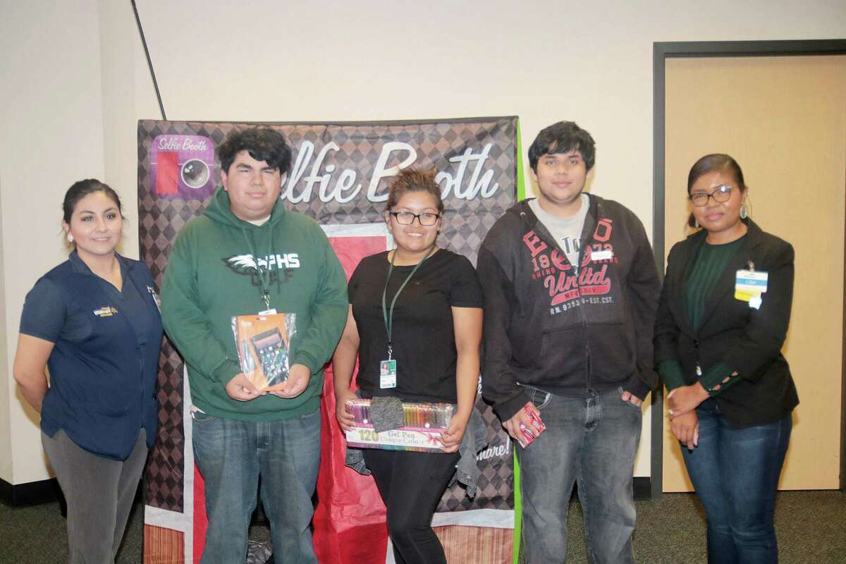 Pasadena High School students Holario Campos, second from the left, Astrit Murillo and Dennis Mesa, flanked by Hoanna Munguia and Lisa Israel from Walmart, receive prizes through a reading program.