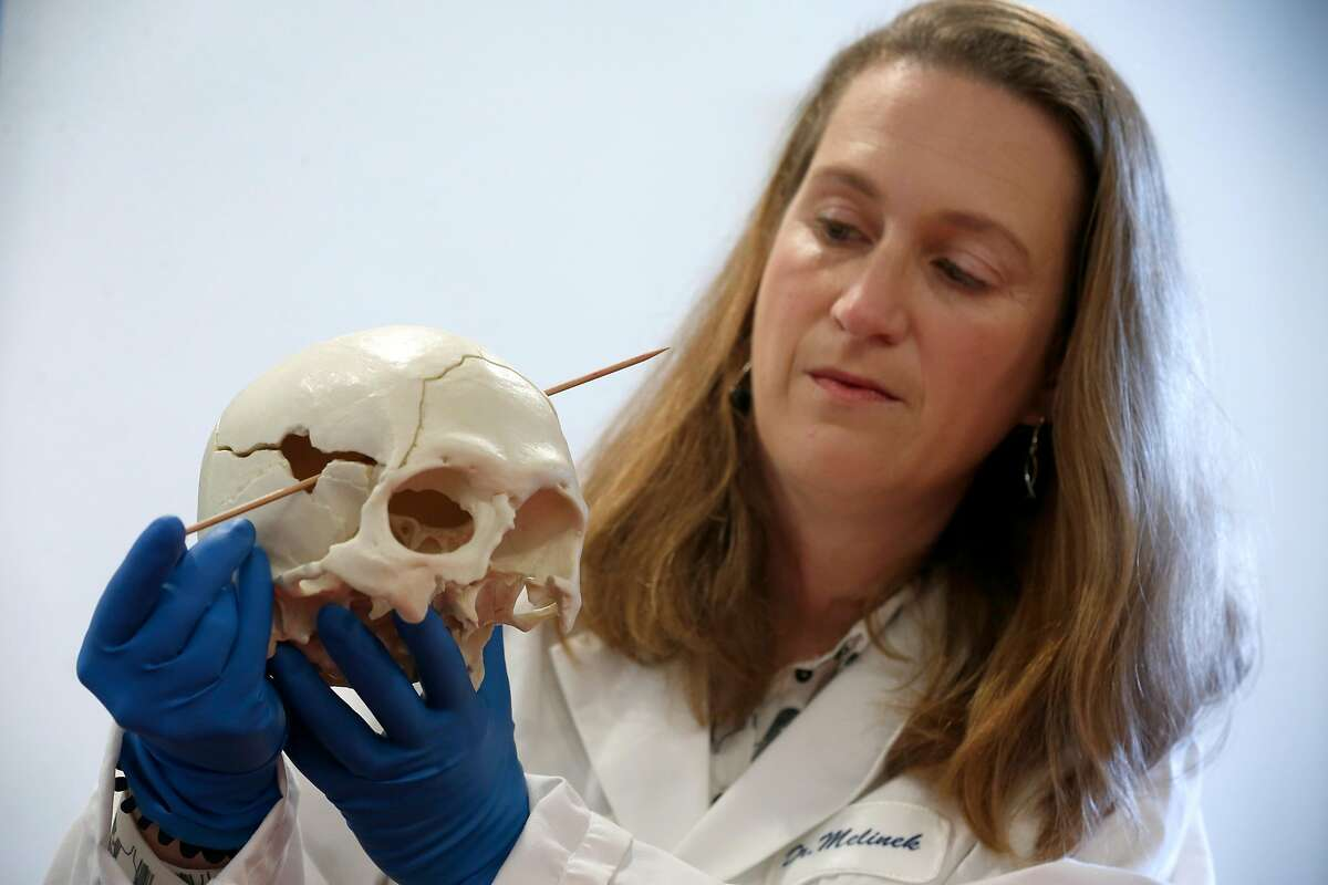 """Pathologist Dr. Judy Melinek inserts a rod to show the trajectory of a bullet in a plastic cast of a gunshot victim's skull at her office in San Francisco, Calif. on Tuesday, Nov. 13, 2018. Dr. Melinek's response to an NRA comment that doctors should """"stay in their lane"""" regarding gun violence went viral after she tweeted it on Friday."""