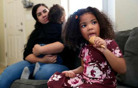 Maipele Burns, 4, enjoys a chocolate ice cream cone while sitting in the living room of her home in Camarillo, Calif.,  with her mother Carlene and brother Elijah, 2, on Oct. 18, 2018.  Maipele was diagnosed at the age of 2 with Acute flaccid myelitis, causing permanent paralysis in her right arm. (Mel Melcon/Los Angeles Times/TNS)
