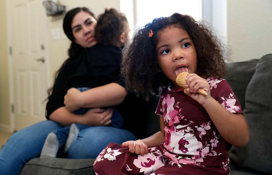 Maipele Burns, whose right arm is parakyzed, eats ice cream while her mother Carlene holds her brother Elija in their Camarillo (Ventura County) home. Photo: Mel Melcon / Los Angles Times / TNS