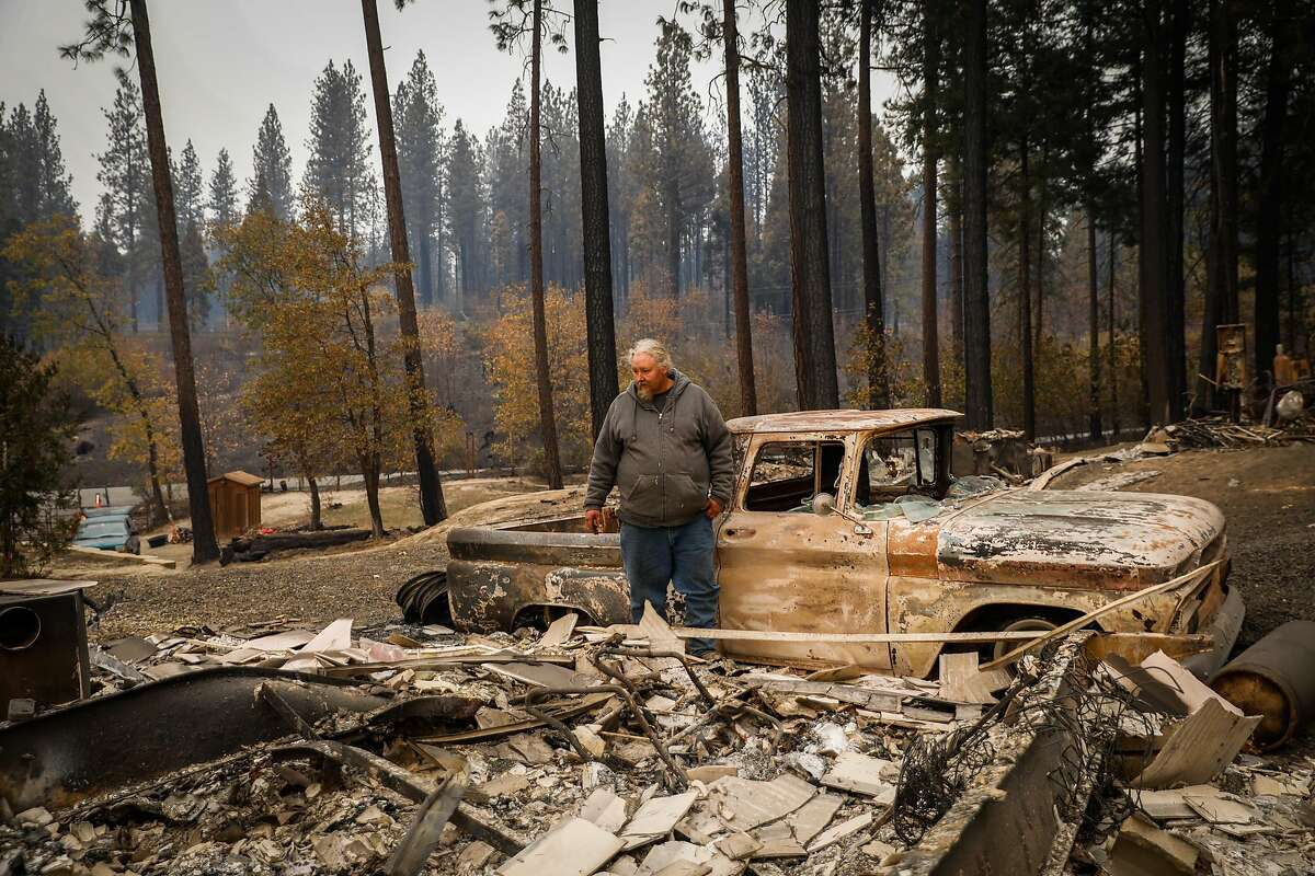 """Troy Miller who survived the Camp Fire in what he called a """"miraculous act of God"""" surveys his destroyed property for a portrait off Concow Road in Concow, California, on Tuesday, Nov. 13, 2018."""