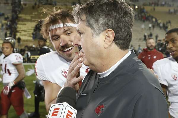Washington State Cougars quarterback Gardner Minshew (16) puts a fake mustache on head coach Mike Leach in the second half of an NCAA college football game Saturday, Nov. 10, 2018, in Boulder, Colo. Washington State won 31-7. (AP Photo/David Zalubowski)