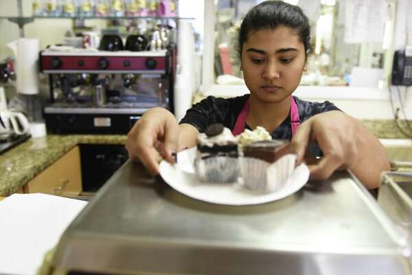 Nasreen Fazal weighs baked goods for a customer at DiMare Pastry Shop in the Riverside section of Greenwich, Conn. Tuesday, Nov. 13, 2018. DiMare is closing the doors for its shop in the Riverside Commons shopping center when its lease is up in early January, but will remain open at 12 Largo Dr. in Stamford.