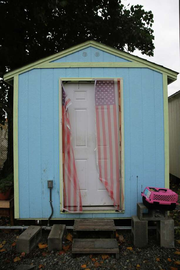 The door of a tiny house at Nickelsville Georgetown is decorated with an unzipped American Flag screen, Oct. 29, 2018. Photo: GENNA MARTIN, SEATTLEPI.COM / SEATTLEPI.COM