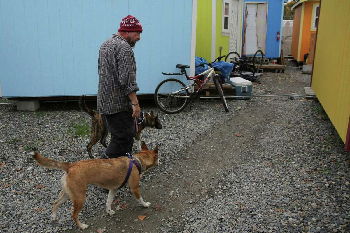 Robert Bowen walks through the Nickelsville Georgetown tiny house village where he has lived with his wife Ashley for the past few months with his two dogs Coral and Opal. Robert believes an influx of affordable housing will help quell the ongoing homelessness crisis in Seattle.
