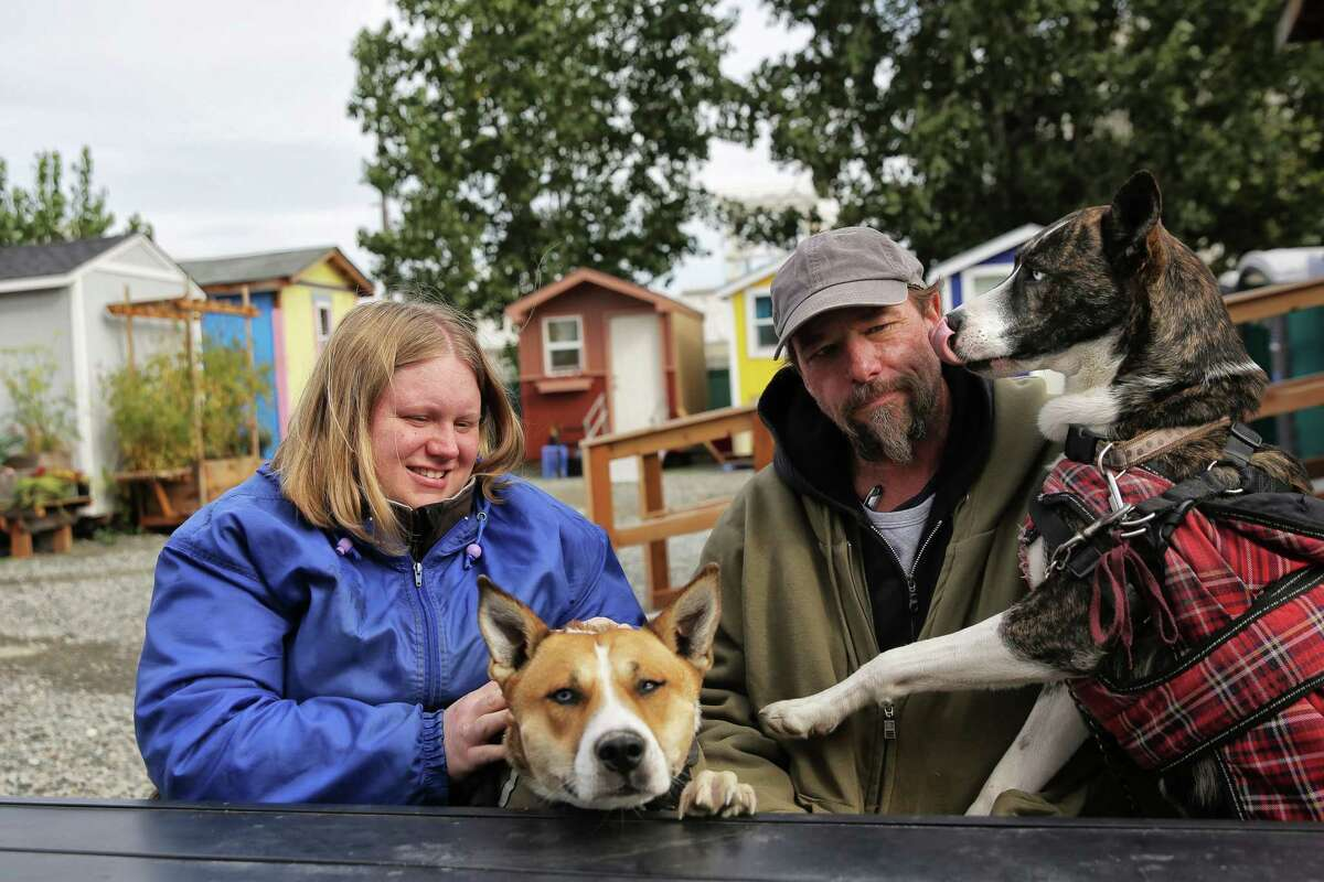 Robert and Ashley Bowen play with their dogs, Opal and Coral, at the Nickelsville Georgetown tiny house village where they have lived for the past few months. Robert believes a major influx of affordable housing will help quell the ongoing homelessness crisis in Seattle.