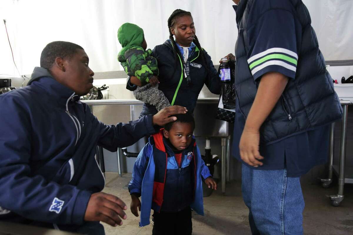Kenyatta Webb, left, talks with his family including 14-year-old son Milchia, right, daughter Brianna and his two grandsons in the kitchen tent at True Hope tiny house village where they all live, Oct. 28, 2018.