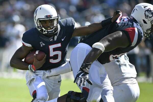 UConn quarterback David Pindell grabs teammate Matt Peart's shirt and is pulled in for a touchdown against Rhode Island on Sept. 15.