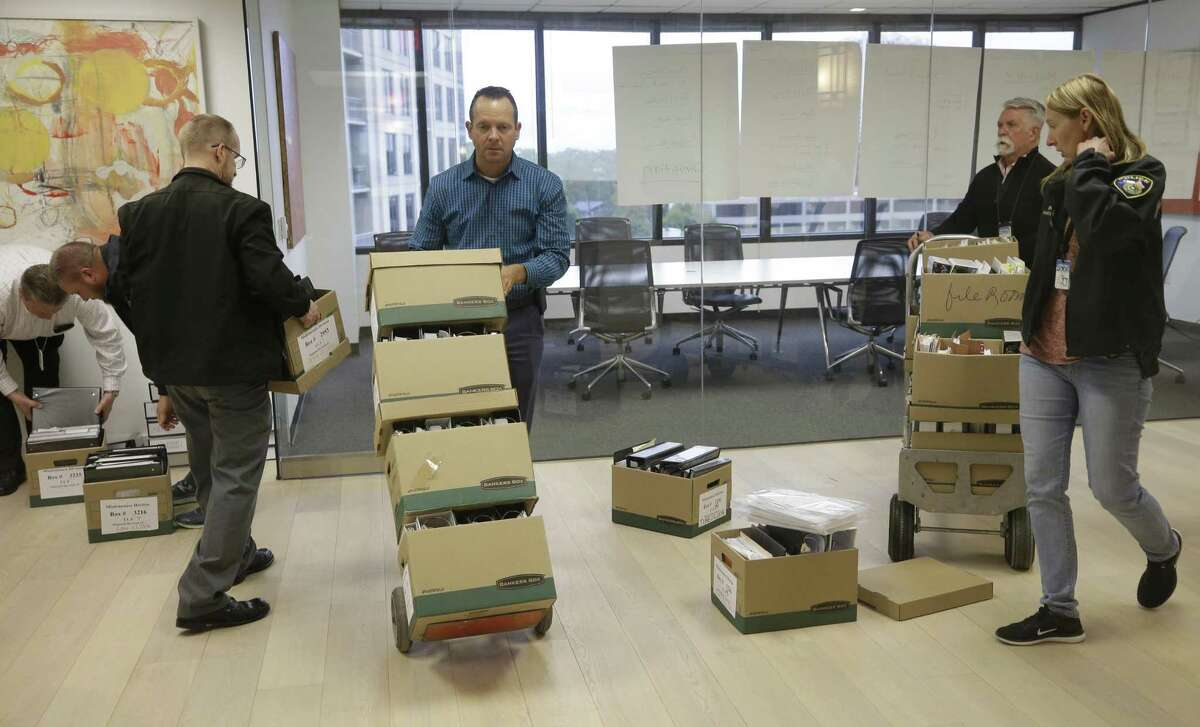 Investigators with the Harris County District Attorney's office load files after serving a search warrant at the Woodfill Law Firm, 3 Riverway #750, Monday, Nov. 12, 2018, in Houston. The founding partner is Jared Woodfill.