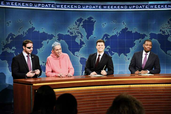"""In this Nov. 10, 2018 photo provided by NBC, Lt. Com. Dan Crenshaw, from left, a congressman-elect from Texas, Pete Davidson, Anchor Colin Jost, and Anchor Michael Che appear during Saturday Night Live's """"Weekend Update"""" in New York. Davidson made his apologies to Crenshaw whose appearance he mocked, saying Crenshaw """"deserves all the respect in the world."""" (Will Heath/NBC via AP)"""