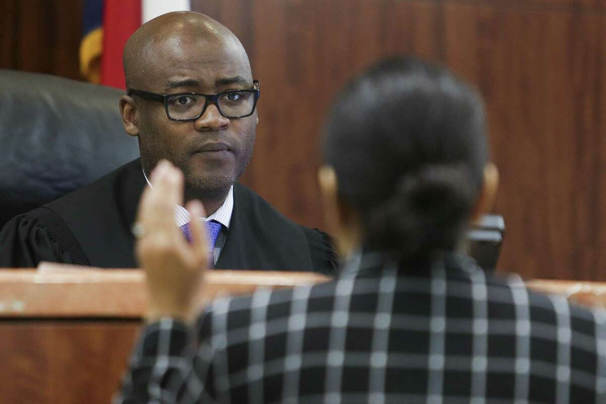 Judge Darrell Jordan, left, goes through his docket at the Harris County Criminal Courthouse Tuesday, May 9, 2017 in Houston. Jordan has testified against other judges in Harris County in a federal lawsuit claiming that by setting high bonds for poor people accused of low-level offenses and pose no danger or flight risk, the system is set up to jail people merely because they are poor. Judge Jordan has abolished the practice in his own courtroom. ( Michael Ciaglo / Houston Chronicle)