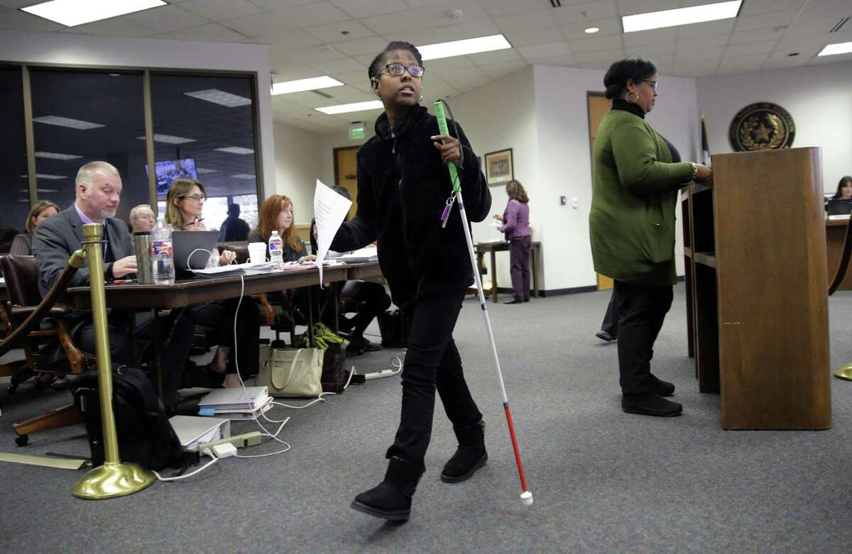 Gabrielle Caldwell, who is partially deaf and blind, returns to her seat after she testified before the Texas School Board during public testimony as they prepares to vote on history curriculum, Tuesday, Nov. 13, 2018, in Austin, Texas. The Republican-controlled board is hearing from activists and academics who are defending or decrying proposed edits meant to streamline academic standards for history. (AP Photo/Eric Gay)