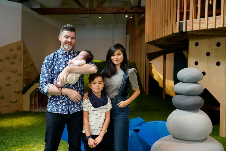 Devin Westberg;  Momoka Westberg, 4 weeks; Kiian Westberg, 8 and Kyoko Westberg stand for a portrait together in the indoor play space at Fox and Kit on Monday, November 12, 2018 in San Rafael, Calif.