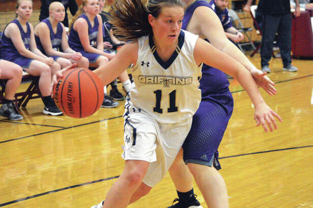Father McGivney junior Macy Hoppes, left, drives to the basket during the second quarter of Tuesday's game against Valmeyer at the Dupo Cat Classic.