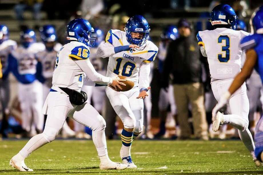 Midlandquarterback Al Money hands off the ball to Christian Gordon as Tommy Johnstone (3) goes in motion during the Chemics' Division 2 regional championship game against Walled Lake Western last Friday. (Katy Kildee/kkildee@mdn.net)