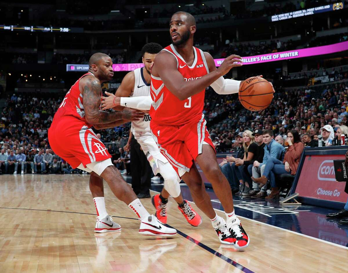 Houston Rockets guard Chris Paul, front, drives to the basket as forward PJ Tucker, back left, blocks Denver Nuggets guard Jamal Murray in the first half of an NBA basketball game, Tuesday, Nov. 13, 2018, in Denver. (AP Photo/David Zalubowski)