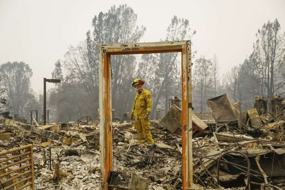 Paradise Firefighter Mike Rea surveys a property for remains at the Paradise Community Village Apartments. Photo: Gabrielle Lurie / The Chronicle / ONLINE_YES