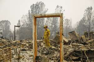 Paradise Firefighter Mike Rea surveys a property for remains at the Paradise Community Village Apartments.