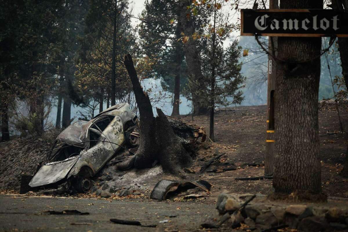 A car is seen burned on the side of Concow Road following the Camp Fire in Concow, California, on Tuesday, Nov. 13, 2018.