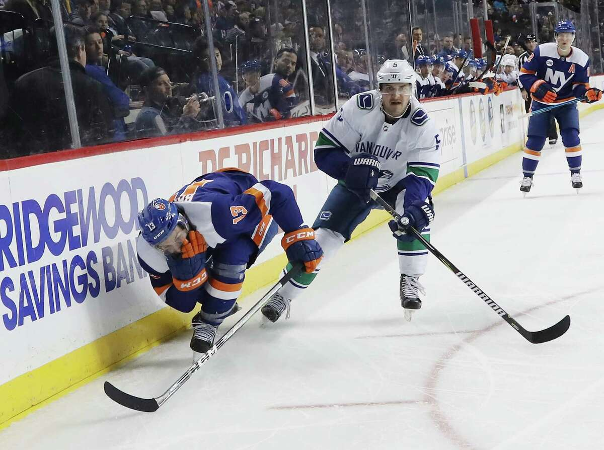 NEW YORK, NEW YORK - NOVEMBER 13: Derrick Pouliot #5 of the Vancouver Canucks takes a second period penalty for high sticking Mathew Barzal #13 of the New York Islanders at the Barclays Center on November 13, 2018 in the Brooklyn borough of New York City. (Photo by Bruce Bennett/Getty Images)