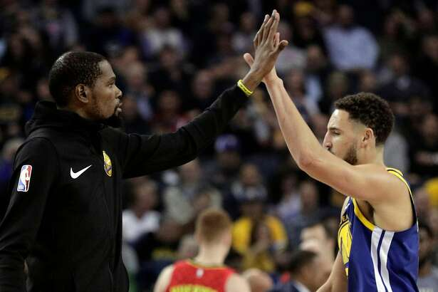 Kevin Durant (35) high fives Klay Thompson (11) in the first half as the Golden State Warriors played the Atlanta Hawks at Oracle Arena in Oakland, Calif., on Tuesday, November 13, 2018.