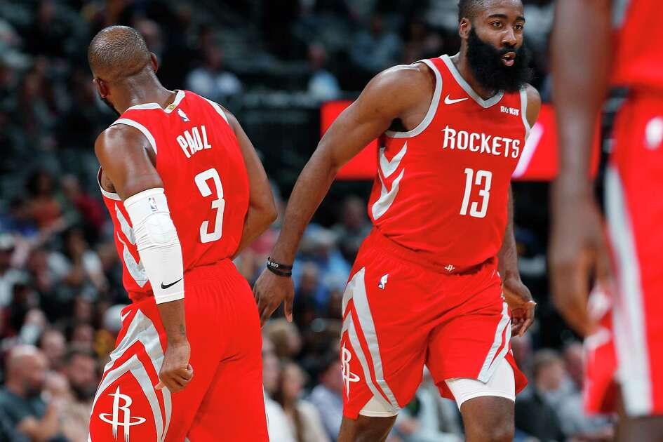 Houston Rockets guard Chris Paul, left, congratulates Houston Rockets guard James Harden after his basket against the Denver Nuggets in the second half of an NBA basketball game, Tuesday, Nov. 13, 2018, in Denver. The Rockets won 109-99. (AP Photo/David Zalubowski)