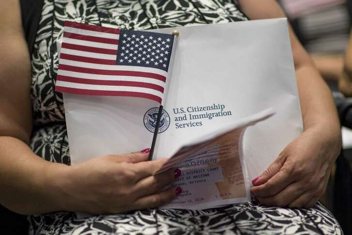 An applicant for U.S. citizenship holds an American flag and paperwork during a naturalization ceremony in Tucson, Arizona, on Sept. 16, 2016. MUST CREDIT: Bloomberg photo by David Paul Morris