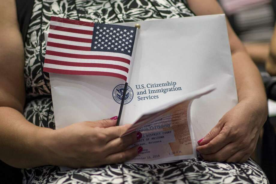 An applicant for U.S. citizenship holds an American flag and paperwork during a naturalization ceremony in Tucson, Arizona, on Sept. 16, 2016. MUST CREDIT: Bloomberg photo by David Paul Morris Photo: David Paul Morris, Bloomberg / Bloomberg / Bloomberg